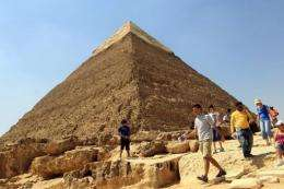 A tourist walks in front the Great Pyramid
