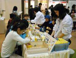 Japanese school children visit a educational workshop at the Eco-Products 2010 exhibition
