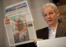 Julian Assange holds up a copy of the Guardian newspaper