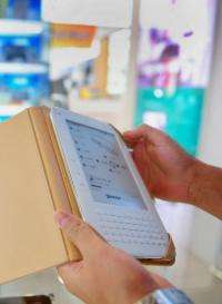 A customer checks out a Chinese-made E-reader at an electronics mall in Beijing
