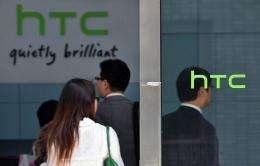 People walk past High Tech Computer Corp. (HTC) logos