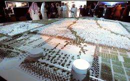 Visitors look at the project model of Masdar City in Abu Dhabi in 2008