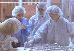 Dr. Eileen Stansbery and other members of the Genesis cleanroom team look at recovered samples