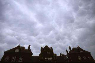 Rare cumulonimbus mammatus clouds hang low in the sky above a silhouetted view of Science Hall on the UW-Madison campus