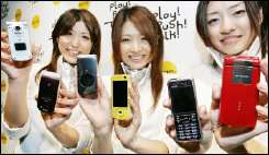 NTT DoCoMo employees unveil the company\'s new 3G handsets