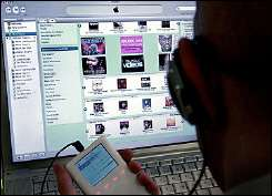 A man holds an iPod as he browses through the iTunes music store online