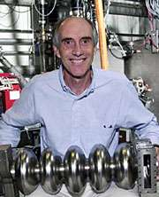 Gwyn Williams holding an accelerator component inside JLab's FEL