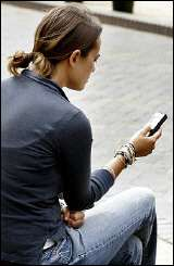 A woman uses her mobile phone to send an SMS text message