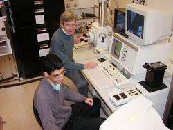 Alireza Nojeh (front) and Fabian Pease use a scanning electron microscope to view carbon nanotubes.