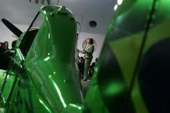 Brazil's Chief of Staff Dilma Rousseff (C, background) delivers a speech next to a 100% ethanol powered aircraft