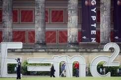 People walk past a giant sculpture featuring Albert Einstein's formula E=mc2