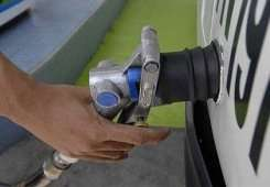 A gas station attendant fills up a car