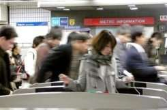 Japanese commuters walk through automated ticket gate of at a Tokyo subway station