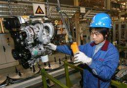 A Chinese automotive worker prepares a 4 cylinder engine for a Chery QQ car at their factory in Wuhu, Anhui Province
