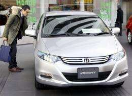 A customer admires a Honda Motor's hybrid vehicle