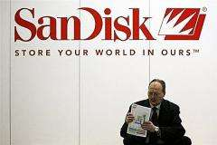A fair-goer sits next to a logo of US data storage giant SanDisk at a technology fair
