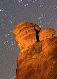 A meteor streaks diagonally across the sky