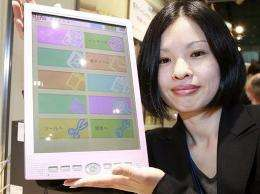 An employee of Japanese computer giant Fujitsu displays the company's mobile information terminal