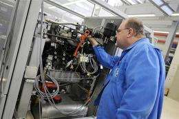 A technician of German automaker Volkswagen's adjusts a mini gas-fired power plant