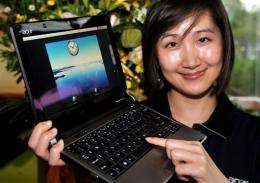 A woman displays a latest Acer UX-30 notebook at Computex Taipei