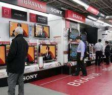 Customers check Sony's Bravia LCD TVs at a shop in Tokyo
