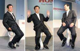 Honda President Takanobu Ito  displays the prototype model of a personal mobility device called the 'U3-X'