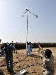 Pakistani technicians install a wind turbine on the island of Kharochhan