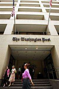 People walk past the Washington Post building in Washington, DC