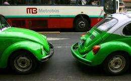 Two vintage beetle Volkswagen taxies pass by a  new