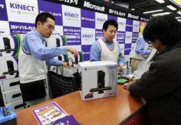 A Japanese customer (R) purchases the Microsoft Xbox 360 Kinect in Tokyo