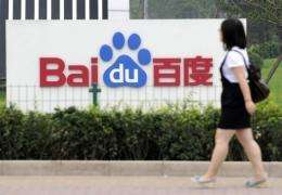 A woman walks past the logo of Baidu at its headquarters in Beijing