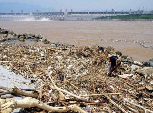 A worker cleans up trash along the banks of the Yangtze River near the Three Gorges Dam