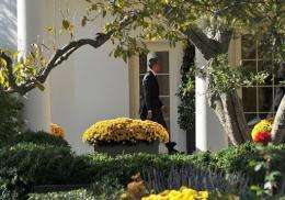 Barack Obama walks to the Oval Office as he returns to the White House