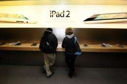 Customers try the latest Ipad 2 at the Apple store on Fifth Avenue in New York