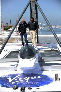 Sir Richard Branson (L) and explorer Chris Welsh stand above a tiny Virgin submarine