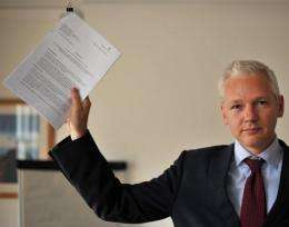 Wikileaks founder Julian Assange holds a legal document as he addresses a press conference in London in July