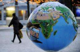 A woman walks past a globe exhibition about combatting global warming and climate change in Copenhagen in 2009