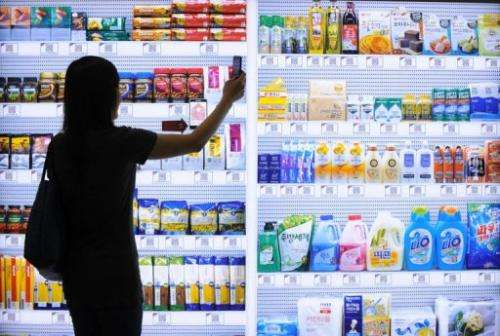A South Korean woman uses her mobile to buy a product at the virtual retail shop at Seolleung subway station in Seoul