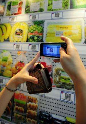 A South Korean woman uses her smartphone to buy a product at the virtual retail shop at Seolleung subway station in Seoul