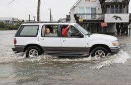 A car drives on a flooded beach road