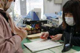 A civic official hands potassium iodide tablets to a woman at a civic building in Iwaki, Japan, in March