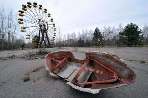 A ferris wheel and an abandoned leisure boat are pictured in a park in the ghost city of Pripyat, near Chernobyl