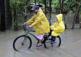 A man cycles across a flooded street with a child in La Libertad, El Salvador