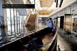 A man drives his boat inside Don Muang airport in Bangkok