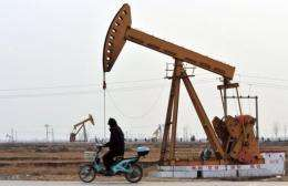 A man riding his scooter ride past oil rigs in Cangzhou, in northern China's Hebei Province, near Bohai Bay, in 2009