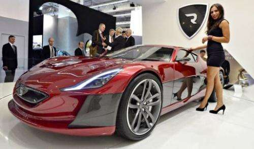 A model poses next to an electric sportscar of Croatian car producer Rimac Automobili
