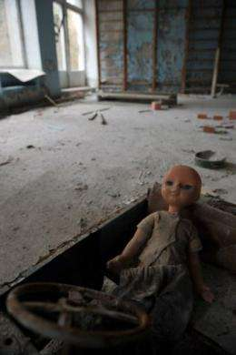 An abandoned plastic doll sits in a child's car at a kindergarden in the ghost town of Pripyat
