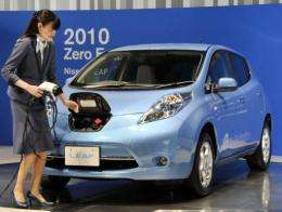 A Nissan employee demonstrates how to plug in the