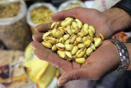 A pistachio wholesaler shows his goods at his shop in Tehran in 2006