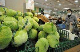 A shopper looks at vegetables at a Tokyo supermarket after a government warning on abnormal radiation levels